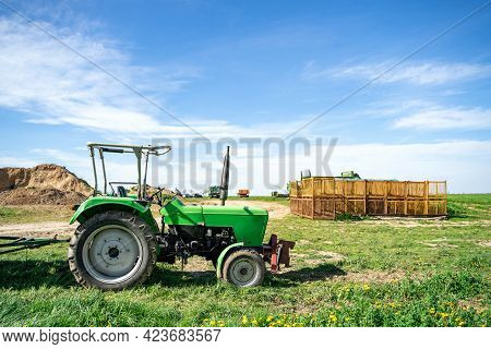 Green Tractor Stands On Farm In Field Near Agricultural Fixtures At Daytime