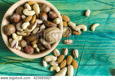 Nuts In Ceramic Dishes And Nuts Scattered On A Green Wooden Background Top View Assorted Nuts
