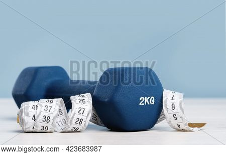 Dumbbell And Measuring Tape On Blue Background