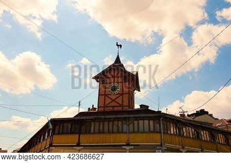Beautiful Ancient Wooden Townhall With Vintage Clock Against Cloudy Sky. Famous Touristic Place And