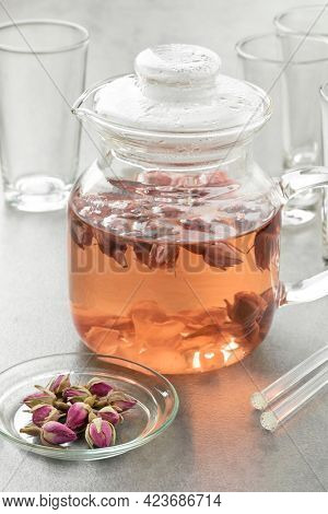 Glass teapot with dried rose buds tea as an aromatic hot drink