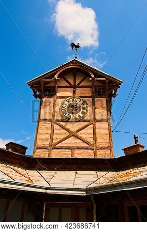Detailed View Of Ancient Wooden Townhall With Vintage Clock Against Cloudy Sky. Famous Touristic Pla