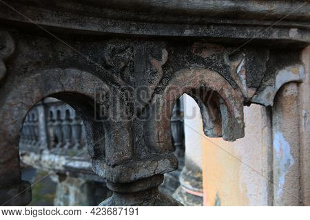 Part Of A Destroyed Balcony In An Old House. Concrete Old Balusters. Wall Showing Signs Of Decay, Cr