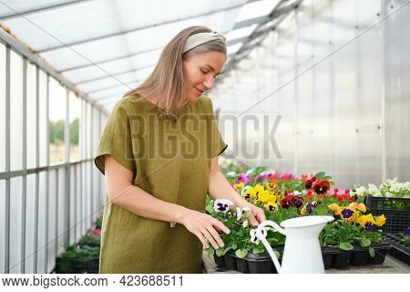 Young Girl In A Linen Dress Admires Flowers In A Greenhouse.