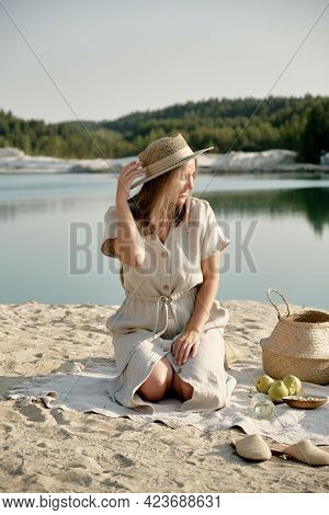 Beautiful Girl In A Linen Dress And Hat Sits Alone On The Shore Of A Pond And Smiles. Vacation, Trav