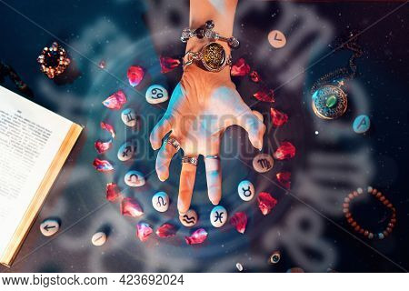 Astrology And Horoscope. A Woman's Hand Conjures Stones With The Signs Of The Zodiac, Laid Out In A