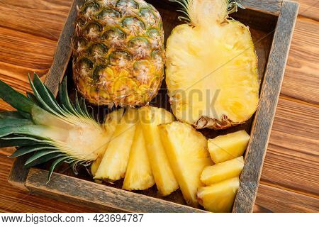 Sliced Pineapple. Tropical Summer Fruit Pineapple Halves And Whole Pineapple On Brown Dark Table In