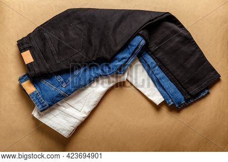 Black White Blue Jeans Pants. Assortment Of Different Color Denim Clothing In Store Shop With Emty L