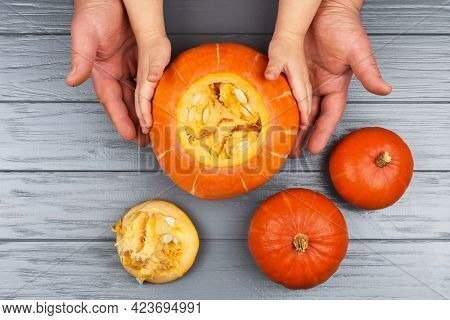 Hands Of A Daughter And Father Who Pulls Seeds And Fibrous Material From A Pumpkin Before Carving Fo