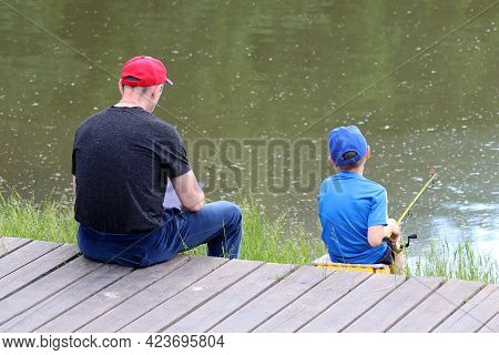 Father And Little Son On A Lake Beach. Child Sitting With A Fishing Rod, Man With Tablet Pc, Rear Vi