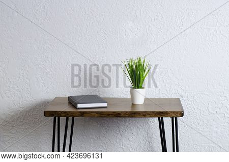 Closed Book And Notepad And Pen. Green Flowerpot In A White Pot On A Wooden Table. Desktop.