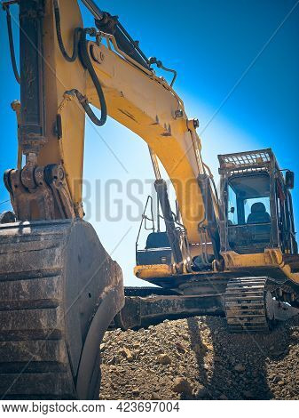 Low Angle View Of Excavator Jib And Scoop. Earthmoving Machinery At Construction Site