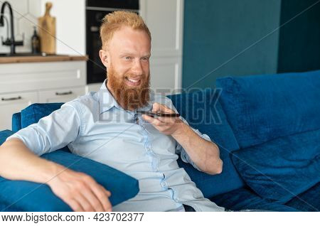 Smiling Young Redhead Man Using Convert Voice Into Text Mobile App, Holding Smartphone And Talking I