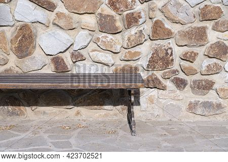 A Vacant Bench By The Stone Wall