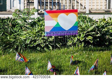 NEW CANAAN, CT, USA- JUBE 13, 2021: New Canaan Pride sign on front  yard near Vine cottage building on Main Street with little pride flags