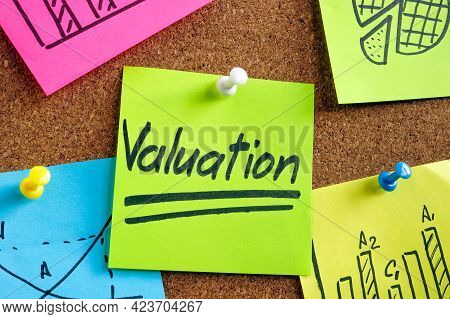 Valuation Word On The Green Sticker Pinned To The Desk.