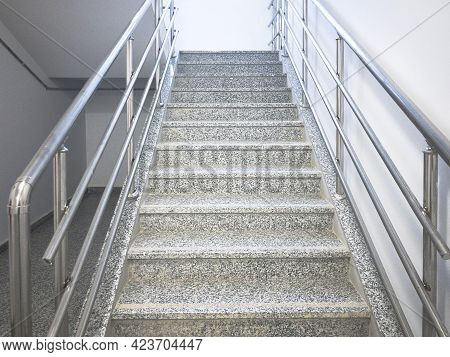 Empty Stairway With Chrome Colored Handrails At Industrial Prefabricated Building.