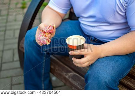 Closeup, A View Of A Bun, A Sweet Doughnut And A Half-drunk Cup Of Coffee, Tea In The Hand Of A Man