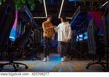 Two young gamers talking in game club