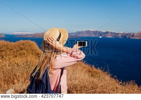 Hiker Woman Walking On Santorini Island, Greece Enjoying Landscape. Happy Traveler Takes Photo Of Se