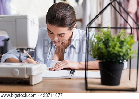 Seamstress Writing On Notebook Near Blurred Plant And Sewing Machine In Atelier.