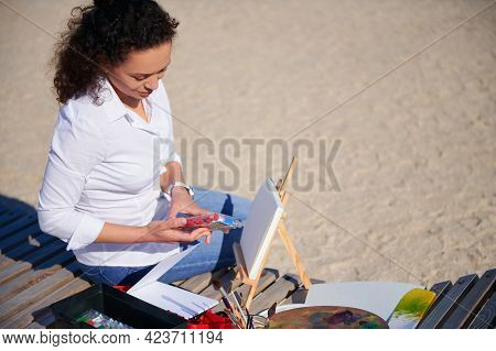 Young Female Painter Opening A Box With Paints Ready To Paint On Canvas In Open Air Sitting On A Woo