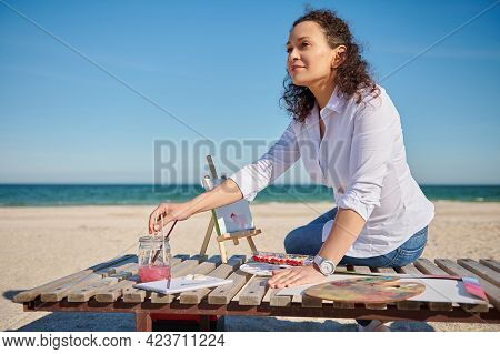 A Beautiful Young Woman Sits On A Wooden Chaise Lounge On The Shore Of The Beautiful Sea And Writes