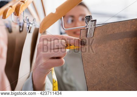 Blurred Designer Measuring Sewing Pattern On Hanger In Atelier.