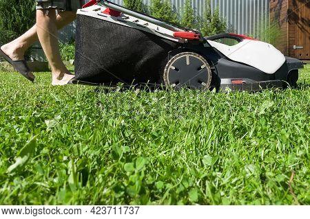 A Man Mows The Tall Grass, Close-up.