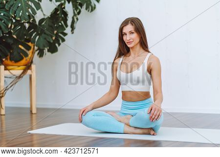 Attractive Young Woman Wearing Sport Bra Sit In Lotus Yoga Position In Light Room And Look At Camera