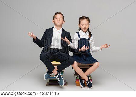 Schoolchildren Meditating While Sitting On Pile Of Books On Grey