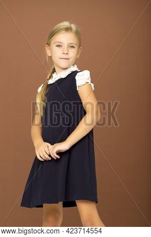 Cute Cheerful Schoolgirl In Uniform. Adorable Blonde Wearing In White Blouse And Blue Dress Standing