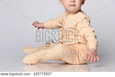 Faceless Little Toddler Toddler Child Sits On The Floor In The Studio In A Cotton Yellow Jumpsuit Fo