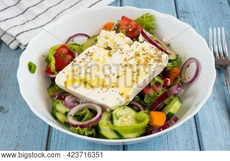Traditional Greek Salad With A Large Piece Of Feta Cheese, Vegetables, Oregano And Olive Oil On A Wo