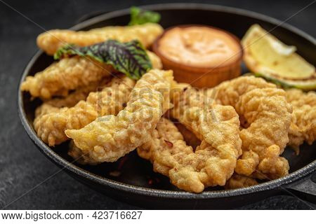 Golden Rings Of Squid Fries In A Round Frying Pan With Sauce, Herbs And Lemon On A Dark Background W