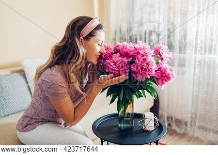 Woman Smelling Peonies Flowers In Vase At Home. Housewife Enjoys Bouquet Of Fresh Pink Blooms. Inter