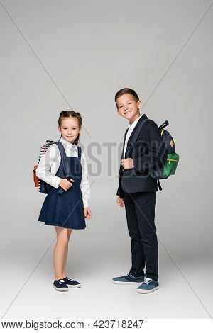 Schoolchildren With Backpacks Standing And Smiling On Grey