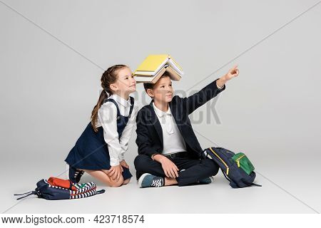 Schoolboy With Books On Head Pointing Away With Finger Near Cheerful Girl On Grey