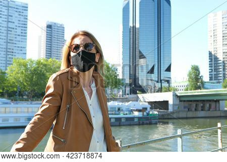 Portrait Of A Blonde Woman With A Surgical Mask In The City. Modern Building Deliberately Blurred In