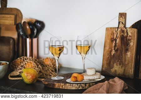 Two Elegant Glasses Of Orange Or Amber Wine And Appetizers