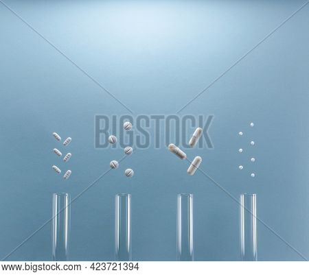 Medical Test Tubes With Various White Tablets, Pills, Pellets, Capsules. On A Blue Background. Flat