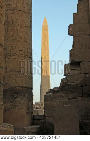 An Ancient Egyptian Stone Obelisk Catching The Golden Sunshine At The Ruins Of The Temple Of Karnak