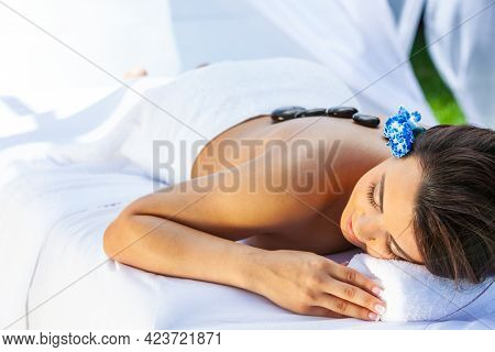A woman with a flower in her hair relaxing at a health spa while having a hot stone treatment or massage