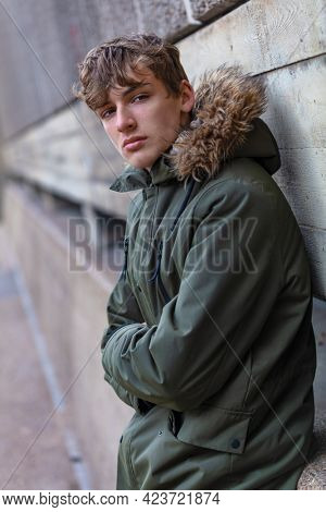 Male young adult teenager wearing a parka jacket outside in modern an urban city environment