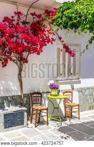 Charming narrow typical streets of Greek islands, Chora town with pink floral tree and coffe table. Cyclades, Greece