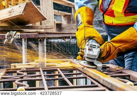 Young Man Welder In A Working Blue Overall And Working Gloves Grinds A Metal Object With A Angle Gri