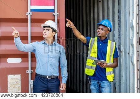 Port Manager And A Colleague Tracking Inventory While Standing Point To Position Loading Containers