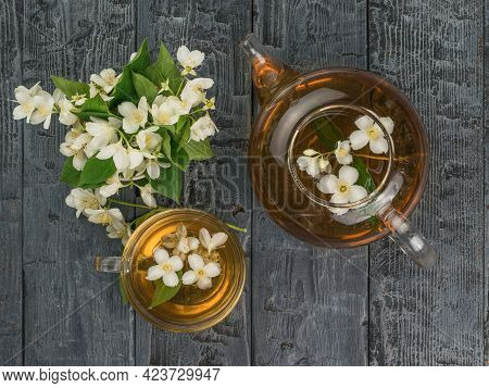 A Glass Teapot And A Cup Of Jasmine Tea On A Wooden Background. An Invigorating Drink That Is Good F