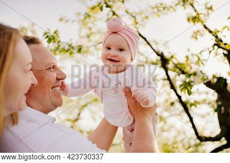 Mom, Dad And Daughter In Spring Flowering Garden. Cleft Lip In Infants.