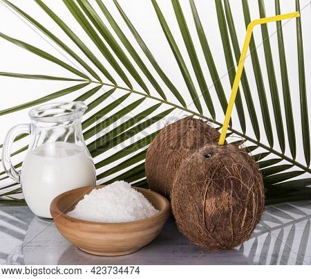 Coconut With A Straw And Coconut Milk In A Jug And Coconut Shavings On A Palm Leaf Background